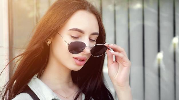 風に揺れる長いゆるい流れる髪とふっくらとした唇のポーズが黒いサングラスのコピースペースを脱いでいるかなりブルネット