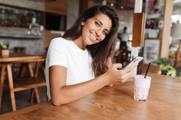 彼女の手に電話を持つかなりブルネットはカフェで休んでいます