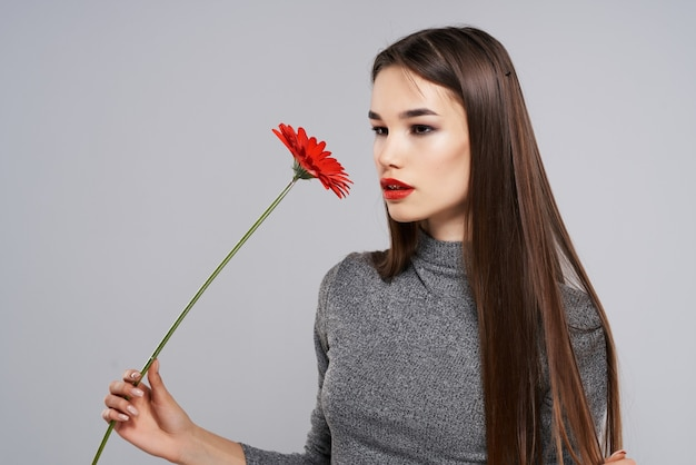 Pretty brunette with red flower bright makeup model