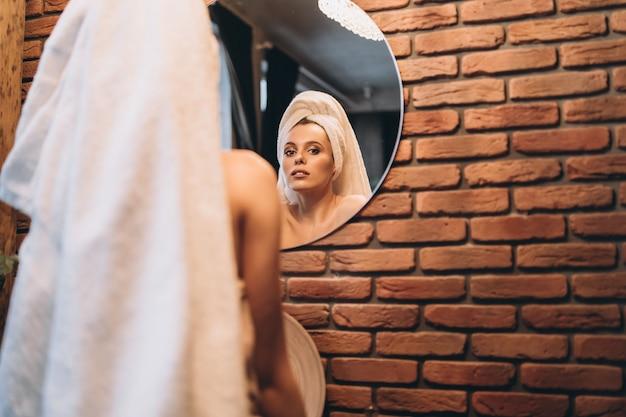 그녀의 수건으로 예쁜 갈색 머리는 샤워 후 화장실에서 거울 근처에 서 있었다