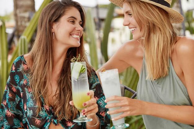かなりブルネットの女性は彼女の親友の女性とカクテルをチャリンと鳴らし、夏休みの後に集まり、ポジティブな印象を共有します。リラックスしたレズビアンのカップルがテラスのカフェテリアで自由な時間を過ごす