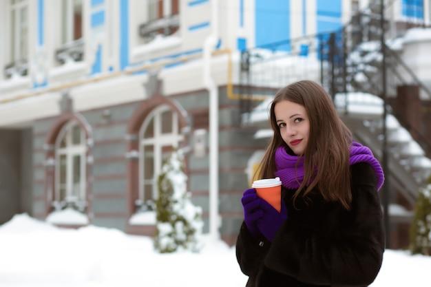 따뜻한 코트와 스카프를 입고 거리에서 차를 마시는 예쁜 갈색 머리 여자