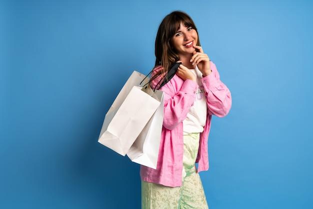 かなりブルネットの女性は買い物を楽しんでいます。幸せな女性のスタイリッシュなイメージ