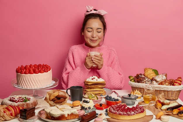 Pretty brunette woman holds glass of milk, eats confectionery and sweets, wears knitted sweater and headband, being sweet tooth poses at festive table against pink background.