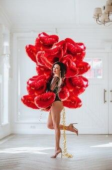 흰 벽에 마음처럼 빨간 풍선의 무리와 함께 포즈를 취하는 블랙 바디에 예쁜 갈색 머리 여자.
