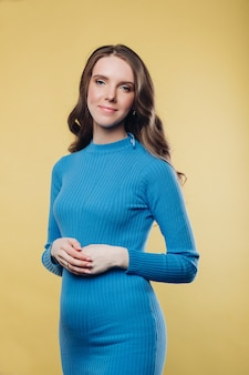 Милая брюнетка в синем хлопковом платье со скрещенными руками на животе