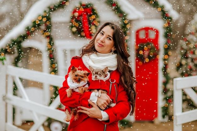 クリスマスの装飾に対してスタイリッシュな服を着たチワワとヨーキーを保持している赤い冬のコートと白いスカーフのかなりブルネットの女性。焦点は女性にあります。雪が降る。休日のコンセプト。