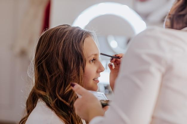 붉은 입술 만들기와 흰 셔츠에 예쁜 갈색 머리 여자는 그녀의 캐비닛에 십 대 소녀에 대 한 확인.