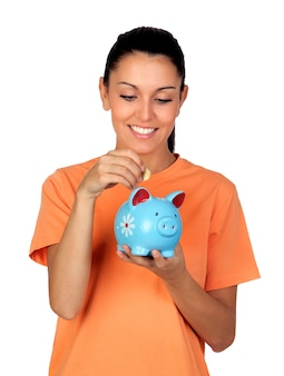 Pretty brunette woman inserting a coin in a piggy-bank isolated on white background