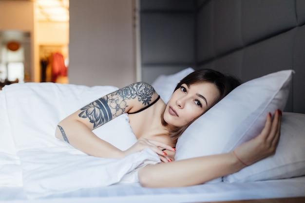 Симпатичная брюнетка лежит в постели утром на подушке в модной современной квартире