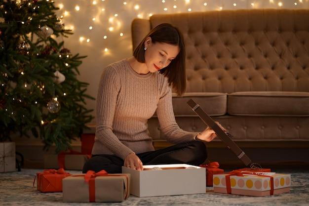 예쁜 갈색 머리 여자는 화이트 크리스마스 글로브를 들고 사랑스러운 선물을 엽니 다