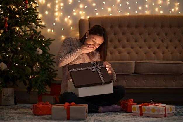 예쁜 갈색 머리 여자는 빛으로 사랑스러운 선물을 엽니 다