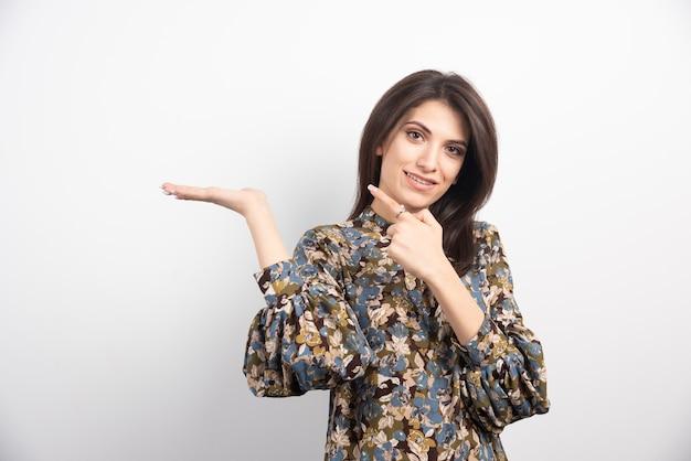 Donna graziosa del brunette che indica su una priorità bassa bianca.