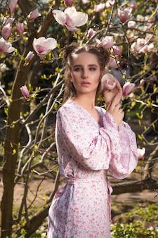 세련된 드레스를 입고 꽃이 만발한 목련 나무 근처에서 포즈를 취하는 예쁜 갈색 머리 여자