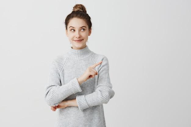 Довольно брюнетка женщина позирует с хитрым взглядом и жесты в сторону. женский дизайнер представляет прекрасный продукт с указательным пальцем. концепция жестов