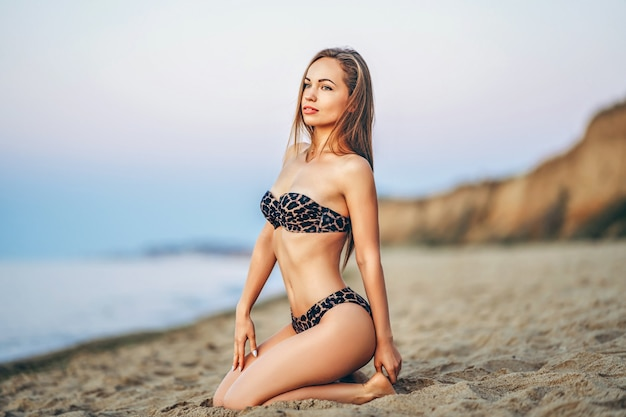 Pretty brunette woman relaxing on the beach at the sea.