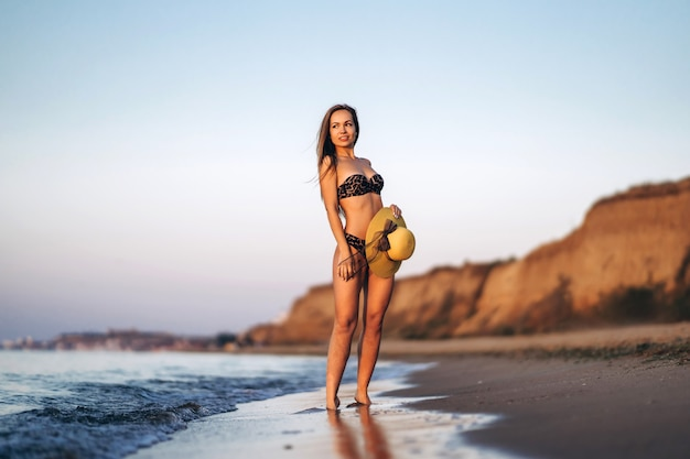 海のビーチでリラックスしたかなりブルネットの女性。