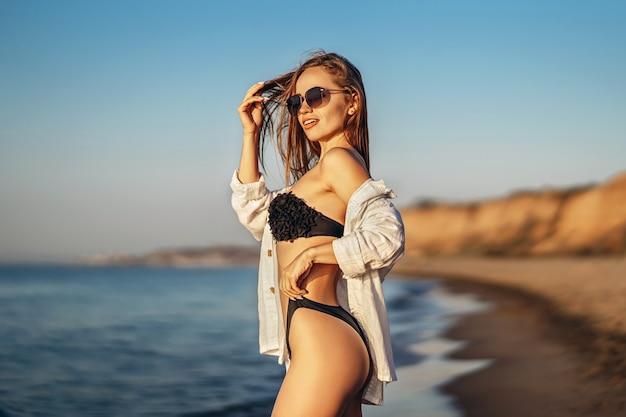 예쁜 갈색 머리 여자는 바다에서 해변에서 휴식.