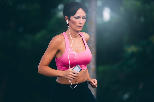 Pretty brunette woman running in a park listening to music