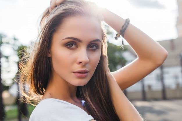 Pretty brunette woman sensual style summer portrait posing outdoor on the street in evening