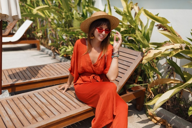 Pretty brunette woman in stylish orange outfit and straw hat chilling on deck chair near pool.