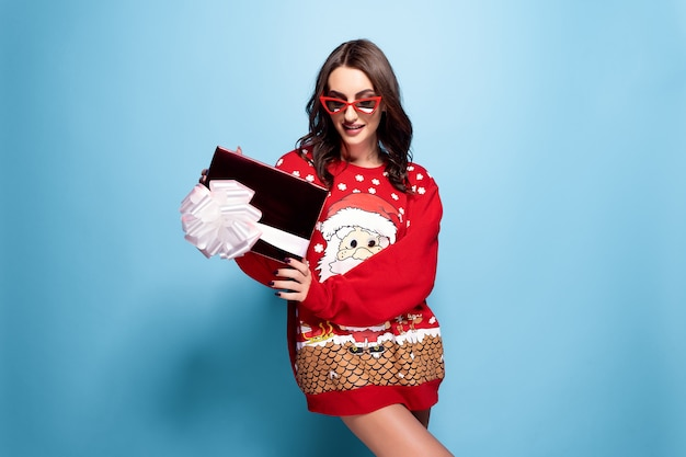 Pretty brunette woman in sunglasses and red oversize pullover with santa design with gift box