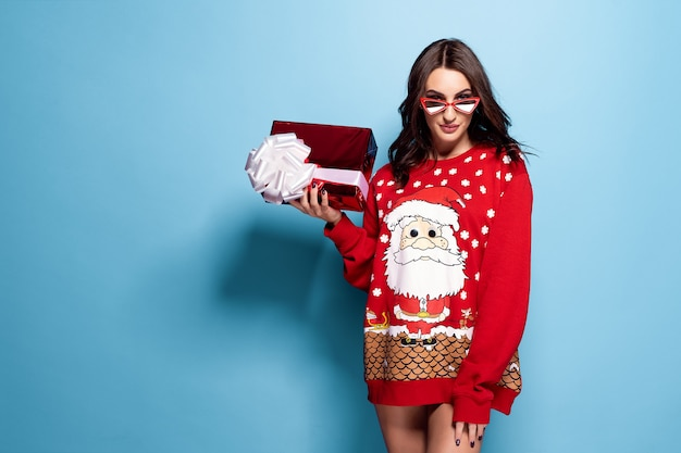 Pretty brunette woman in sunglasses and red oversize pullover with santa  with gift box on blue