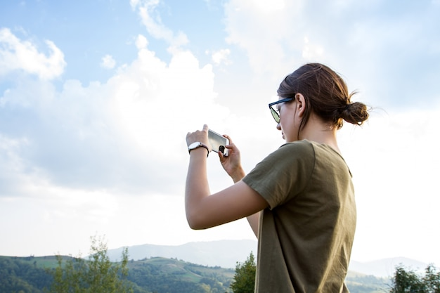 Pretty brunette woman traveling, taking photo of beautiful mountains view