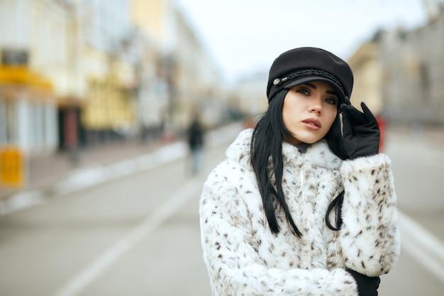 スタイリッシュなキャップと暖かいコートを着ているかなりブルネットの女性