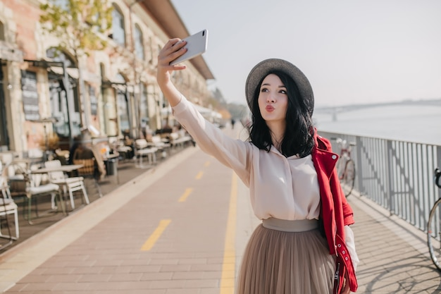 Pretty brunette woman wears elegant blouse and skirt making selfie with kissing face expression