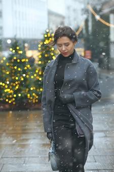 Симпатичная брюнетка в модном пальто гуляет по городу, украшенному к рождеству, во время снегопада
