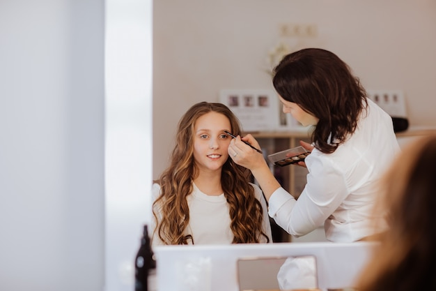 Pretty brunette woman in white shirt with red lips making make up for a teen girl in her cabinet.