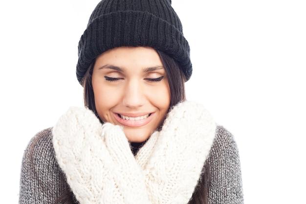 ウールの帽子と寒いセーターと手袋を持つかなりブルネットの女性
