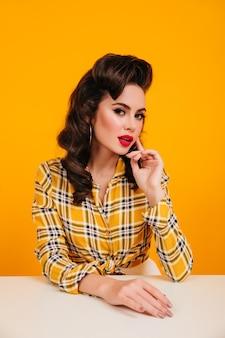 테이블에 앉아 밝은 화장으로 예쁜 갈색 머리 여자. 노란색 배경에 포즈 잘 생긴 핀 업 소녀의 스튜디오 샷.