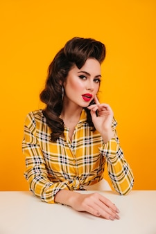 Pretty brunette woman with bright makeup sitting at table. studio shot of good-looking pinup girl posing on yellow background.