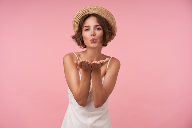 Pretty brunette woman with casual hairstyle raising palms and blowing air kiss, wearing white summer dress and straw hat while posing