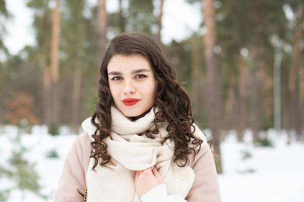 長い髪のかなりブルネットの女性は冬にコートを着ています