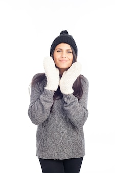 Pretty brunette woman with a woolen hat a sweater and gloves smiling and cheerful