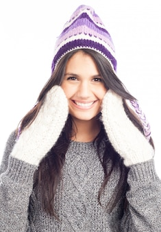 Pretty brunette woman with a woolen peruvian hat a sweater and gloves smiling and cheerful