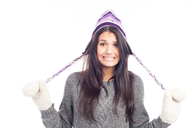 Pretty brunette woman with a woolen peruvian hat a sweater and gloves that has cold