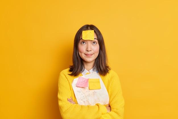Pretty brunette young asian female student tries to remember material for exam has deadline memo sticker stuck on forehad concentrated above stands crossed hands