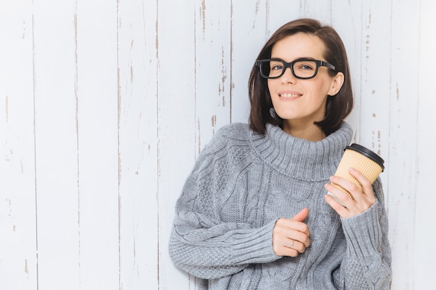 Pretty brunette young female in knitted warm sweater, holds hot drink in paper cup, tries to warm herself in cold winter day