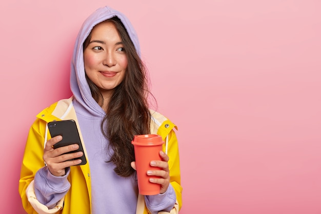 Pretty brunette young woman with natural beauty, uses modern cellphone for chatting with friends, holds takeaway coffee