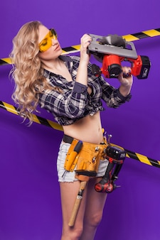 Pretty builder girl in checkered shirt, glasses and white shorts stand with electro saw
