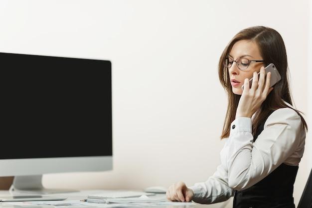 정장을 입고 안경을 쓰고 책상에 앉아 있는 예쁜 비즈니스 여성, 가벼운 사무실의 현대적인 컴퓨터에서 일하고, 문제를 해결하는 휴대 전화로 이야기합니다. 텍스트에 대 한 장소