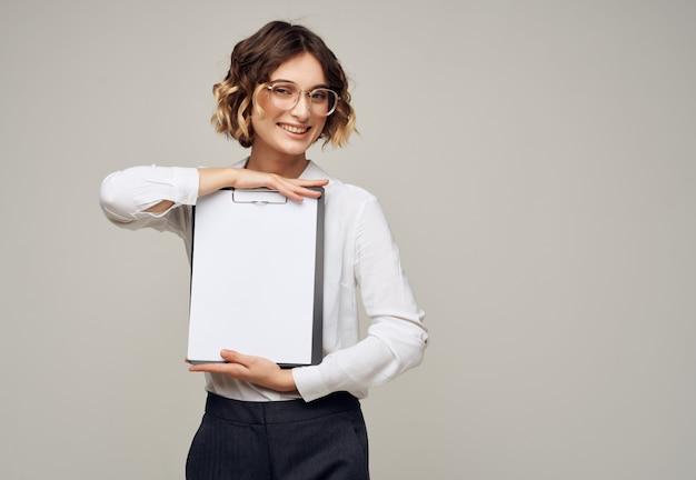 手のコピースペース広告の白いシャツフォルダーのきれいなビジネスウーマン。高品質の写真