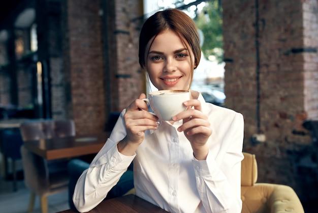 白いシャツを着たかわいいビジネスウーマンが一杯のコーヒーと一緒にカフェに座っています