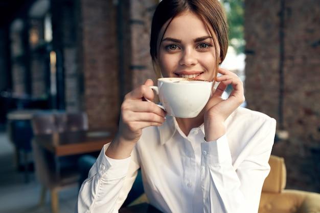 흰 셔츠에 예쁜 비즈니스 우먼 커피 한잔과 함께 카페에 앉아