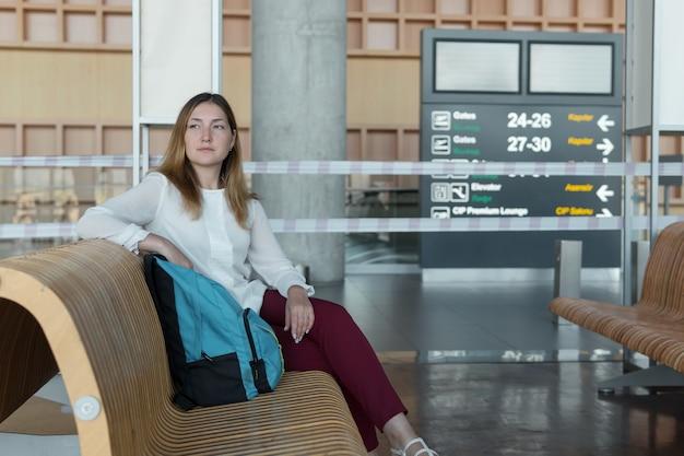 배낭을 메고 있는 예쁜 비즈니스 우먼은 비행기를 기다리는 동안 앉아 있습니다.