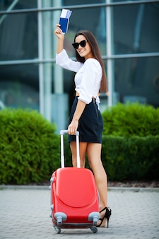 Pretty business woman with red suitcase near airport